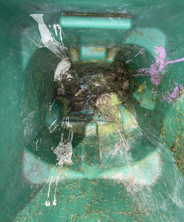 The interior of a filthy trash can